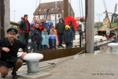 De familie van der Gracht met aanhang ,en (l) schipper Peter Lock, kort voor de afvaart met de loodsbotter Texelstroom. Gelukkig voor het gezelschap knapte het regenachtige weer kort na vertrek weer helemaal op.