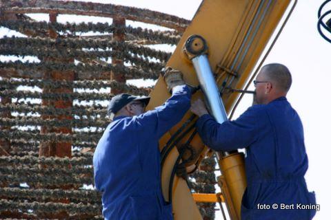 Schipper Dirk Schagen (l) en Silvan Hoep herstellen de kraan op de 'Verwachting'. Waarmee de zware mosselkorven aanboord gehesen worden en in zee worden geplaatst.