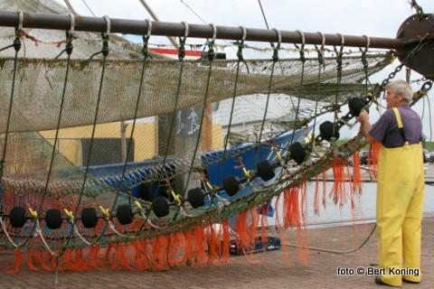 Albert Blom van de garnalenkotter TX 24  'Heliomare'' bezig op de lange dam met het herstellen van het netwerk.