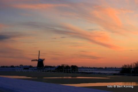 De kleurige zonsondergang bij de molen 't Noorden nabij Oost kondigt strenge vorst aan voor de nacht van zondag op maandag.