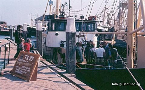 De 'Lida Marco' van Adrie Hutjes na de rondvaart met toeristen aan de kade in de noorderhaven. Aan dek stond een aqarium voor de bijzonder vangsten op de Waddenzee. Rond het aqarium ondermeer TX 44 opvarende: Peter van Efferen(l), Adrie Hutjes en geheel rechts Frans Zoodsma