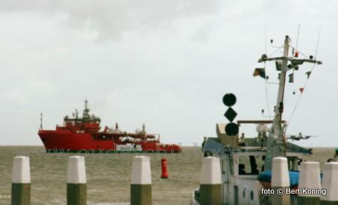 Terwijl de ploegboot 'Aquanaut' uit Urk naar buit komt passert voor de haven van Oudeschild de 57- meter lange 'Esvagt Don'. Het onder Deense vlag Kustwachtschip, met als thuishaven Den Helder,  kwam hier in dienst na de heftige brand op zijn voorganger de 'Waker'. Welke op 7 september 2009 benoorden Vlieland een machinekamerbrand had.